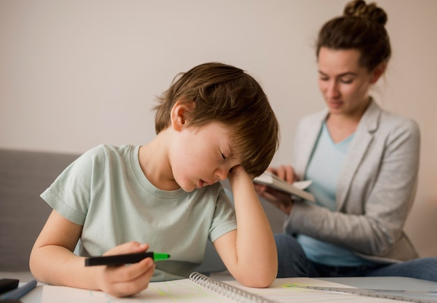 Criança que está cansada enquanto ensina em casa