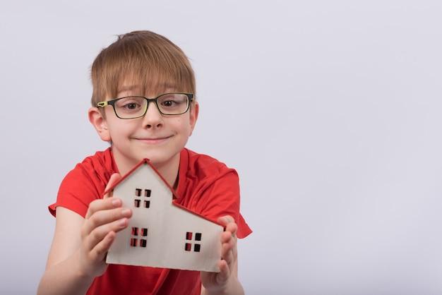 Criança que guarda o modelo da casa no espaço em branco. garoto bonito de óculos, segurando a casa de brinquedo. educação escolar em casa