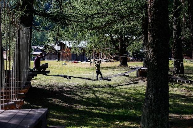 Criança que joga em um parque da aventura da família em uma floresta européia.