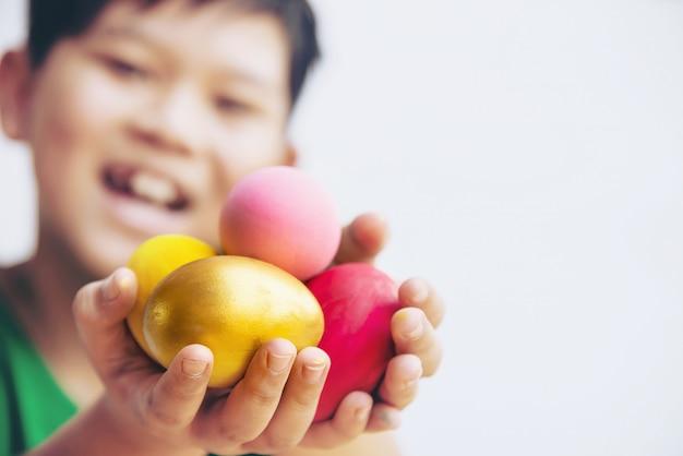 Criança que mostra ovos da páscoa coloridos felizmente - conceito da celebração do feriado da páscoa