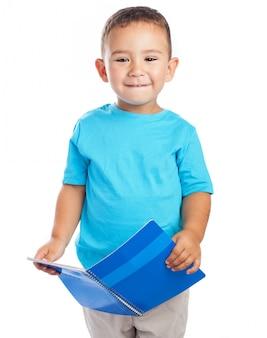 Criança que prende um caderno aberto