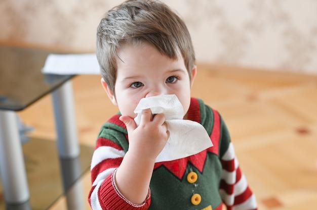 Criança que sofre de corrimento nasal ou espirros. garotinho alérgico