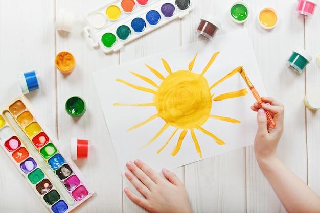 Criança que tira o sol amarelo.