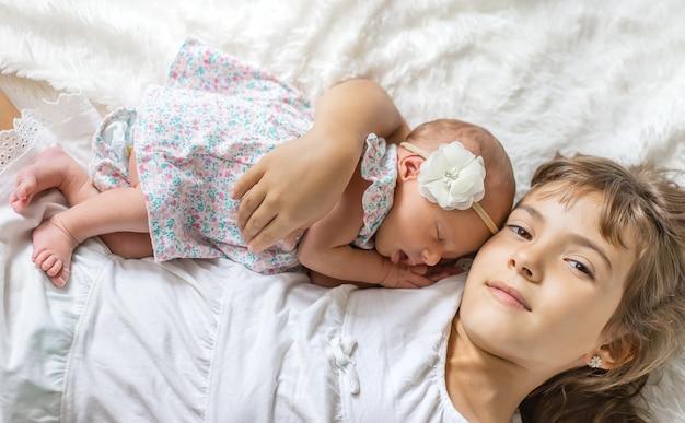 Criança recém-nascida com irmã mais velha