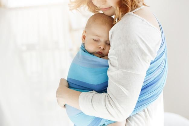 Criança recém-nascida pequena fechar os olhos e ter um bom sono no estilingue do bebê, sentindo a proteção de sua linda jovem mãe. família, conceito de estilo de vida.