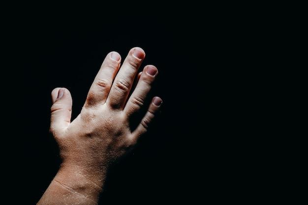 Criança rezando com as mãos no escuro