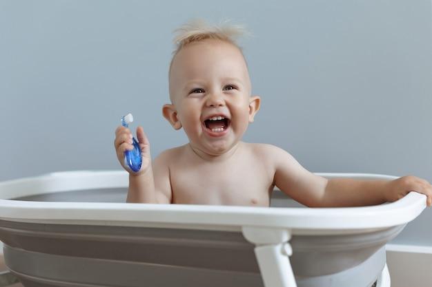 Criança rindo apressando os dentes enquanto está sentada no banheiro