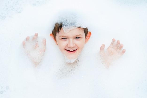Criança rindo cercada por espuma de bolha toma um banho.