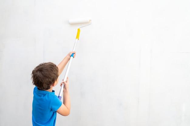 Criança rola o rolo na pintura na parede.