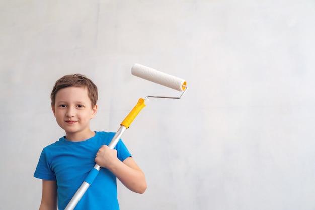 Criança rola o rolo na pintura na parede