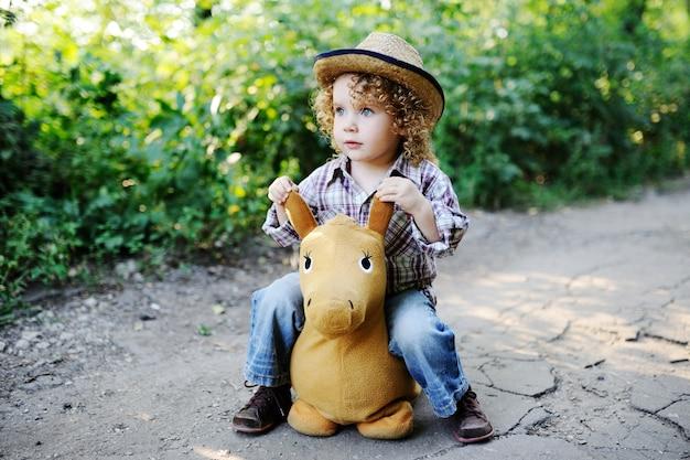 Criança ruiva cacheada em um chapéu de palha