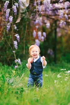 Criança ruiva em pé sobre uma grama verde com uma árvore wysteria ao fundo