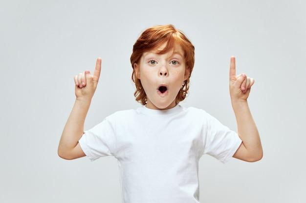Criança ruiva mostra o dedo indicador para cima e camiseta branca