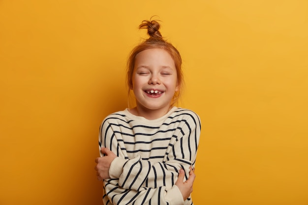 Criança ruiva se abraça, expressa amor próprio, fecha os olhos de prazer, veste um macacão listrado, posa contra a parede amarela, se sente bem, mostra os dentes brancos, cheia de emoção