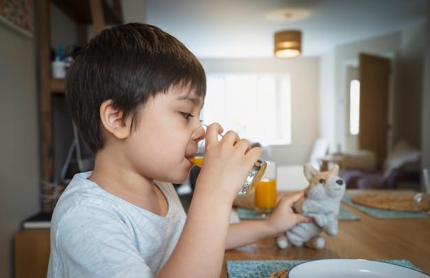 Criança saudável, bebendo suco de laranja fresco de vidro transparente e brincando com seu brinquedo