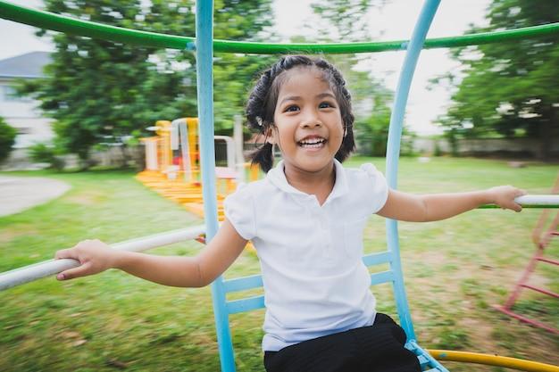 Criança saudável está brincando no quintal, feliz com os balanços, cavalos de balanço, carruagens de slides.