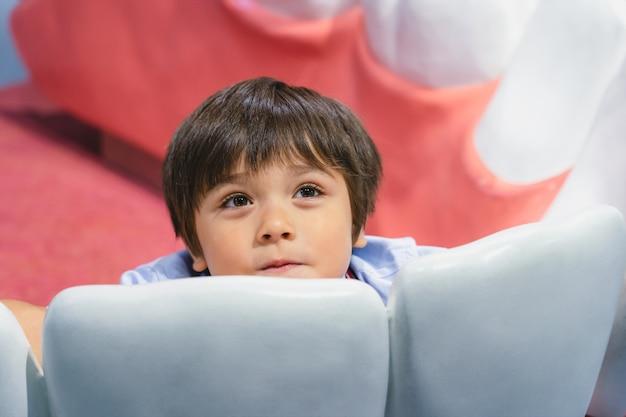Criança saudável sentada dentro de um modelo de dentes brancos