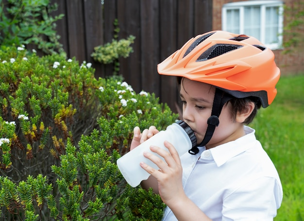Criança saudável, vestindo uma bicicleta capacete água potável.