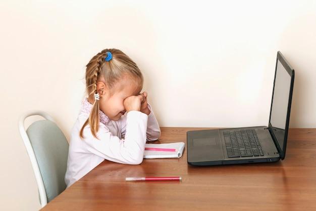 Criança se cansa de estudar online a menina esfrega os olhos enquanto está sentada em frente a um laptop