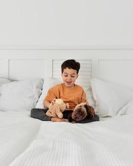 Criança se divertindo com seus brinquedos na cama