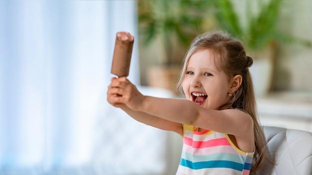 Criança se senta à mesa com sorvete no palito em cobertura de chocolate com recheio rosa