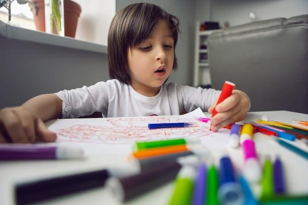 Criança se senta em casa em uma mesa e desenha com marcadores coloridos em um lençol branco