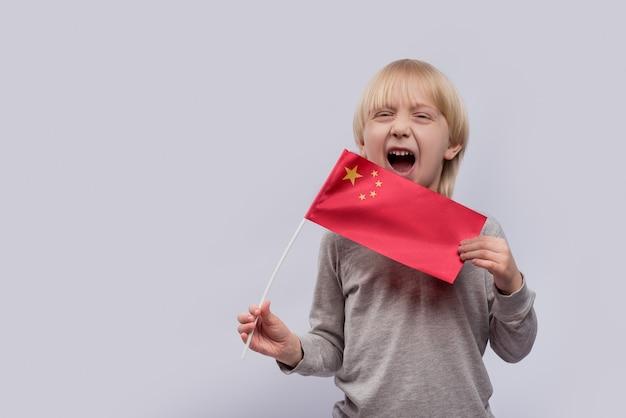 Criança segura a bandeira da china