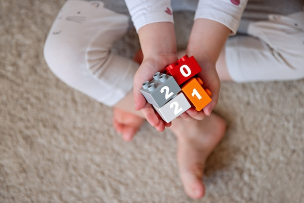 Criança segura nas palmas dos blocos mãos de criança com brinquedo de tijolos