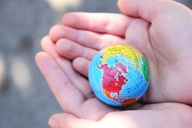 Criança segura o planeta terra nas mãos