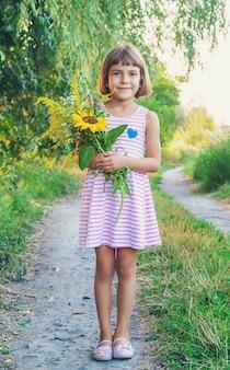 Criança segura um buquê de flores silvestres nas mãos