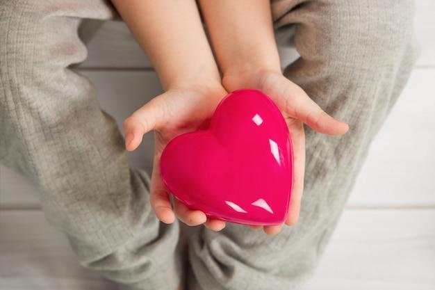 Criança segura um coração vermelho.