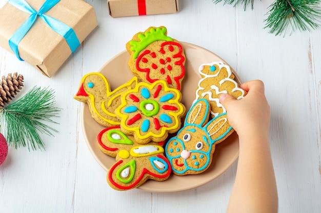 Criança segura um pão de mel pintado caseiro (cookie) sobre fundo branco de madeira entre ramos de abeto e presentes. conceito de presente doce de natal e ano novo. close-up engraçado comida doce.