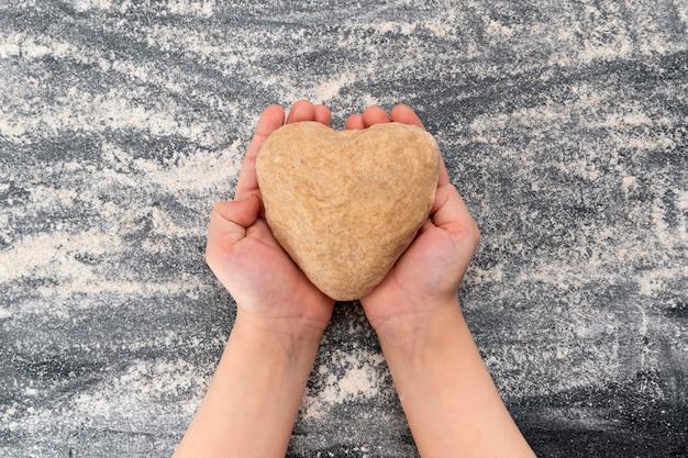 Criança segura uma massa em forma de coração. biscoitos caseiros com amor.
