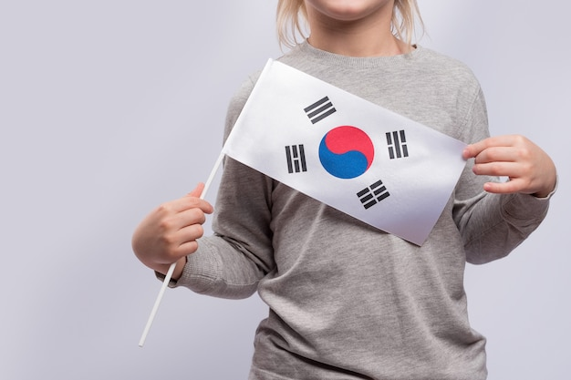 Criança segurando a bandeira da coreia do sul