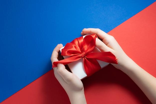 Criança segurando a caixa de presente com laço vermelho grande na moda azul e vermelho