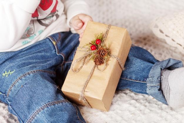 Criança segurando a caixa de presente de natal