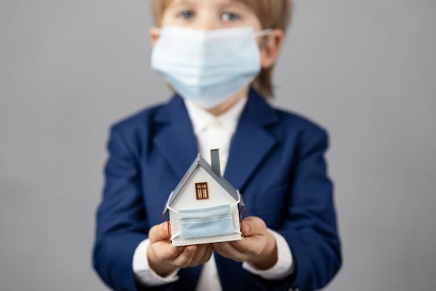 Criança segurando a casa modelo usando máscara médica protetora nas mãos. negócios durante o conceito de pandemia de covid-19 de coronavírus