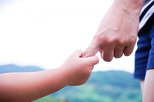 Criança segurando a mão de uma mãe.