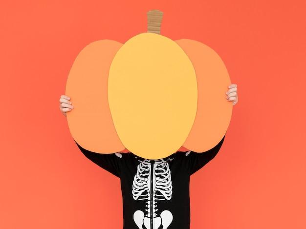 Criança segurando abóboras de halloween