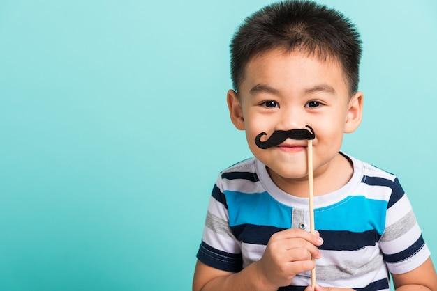 Criança segurando adereços de bigode preto para a cabine de fotos