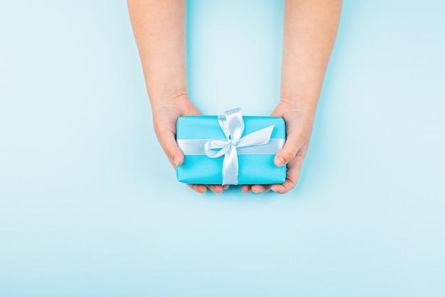 Criança, segurando as mãos caixa de presente azul na mesa