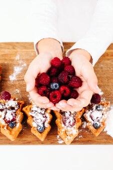 Criança segurando as palmas das mãos de frutas frescas