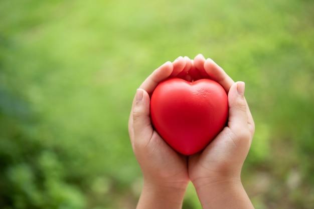 Criança segurando coração de borracha vermelho
