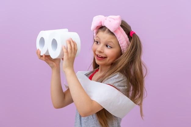 Criança segurando dois rolos de papel higiênico em fundo roxo claro