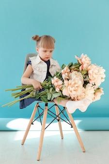 Criança segurando grande buquê de flores
