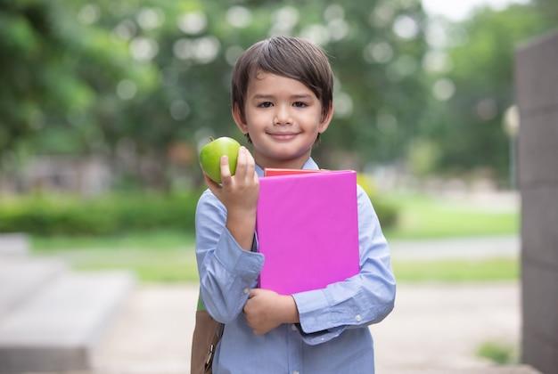 Criança segurando maçãs e livro pronto para ir para a escola novamente
