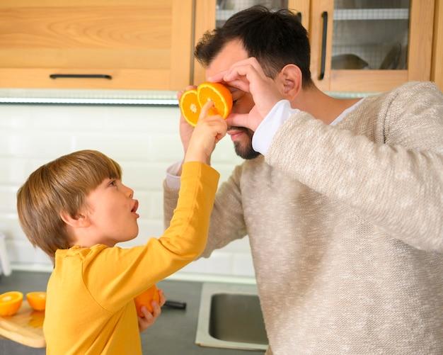 Criança segurando metades de laranjas para seu pai
