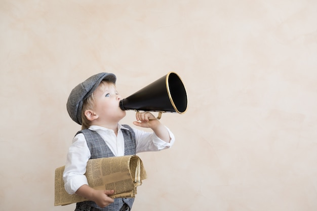 Criança segurando o alto-falante e o jornal. garoto gritando através do megafone vintage. conceito de notícias de negócios