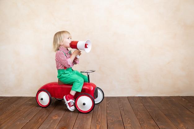 Criança segurando o alto-falante. garoto gritando através do megafone vintage. conceito de notícias de negócios
