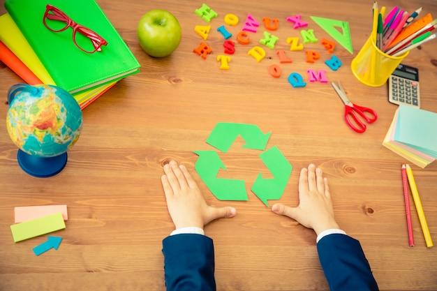 Criança segurando o símbolo de reciclagem nas mãos itens escolares na mesa de madeira na classe conceito de educação